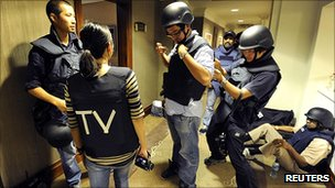 "Journalists mark their flak jackets with ""TV"" initials"
