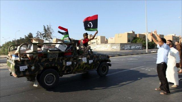 Rebel fighters in Libya wave a flag