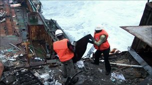 Two workers dismantle a shipwreck in Nigeria
