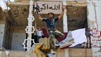 A rebel fighter celebrates as he sits on top of the monument