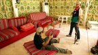 Libyan rebels take souvenir pictures inside the tent where Libyan leader Muammar Gaddafi used to receive foreign visitors