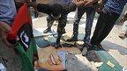 Rebel fighters chant slogans and tear up a portrait of Muammar Gaddafi in his Bab al-Aziziya compound