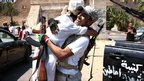 Libyan rebel fighters hug each other as they celebrate in the newly named Martyr's Square, formerly known as Green Square