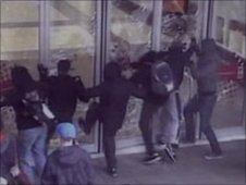 Rioters kicking shop window