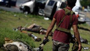A rebel fighter walks past the bodies of pro-Gaddafi troops in Tripoli, Libya (25 Aug 2011)