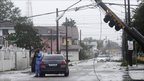 A man photographs a downed utility pole in Nassau