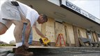 A man in North Carolina boards up a store window