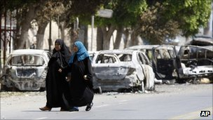 Libyan women walk by burned cars in Tripoli, Libya, Thursday, Aug. 25, 2011