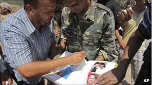 Rebels look through Condoleezza Rice photo album found in Col Gaddafi's Tripoli compound - 24 August 2011