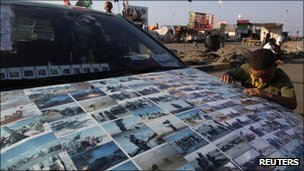 A boy looks at photos of Libya's civil war stuck on the bonnet of a car in Tahrir Square in Benghazi, Libya