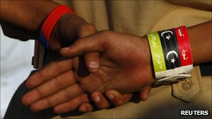 A yount boy who intends to join the Libyan rebel forces, wears a wristband with the Kingdom of Libya flag on it while listening to rebel soldiers in Benghazi