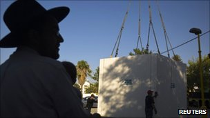 A crane lowers a bomb shelter as a local man looks on.