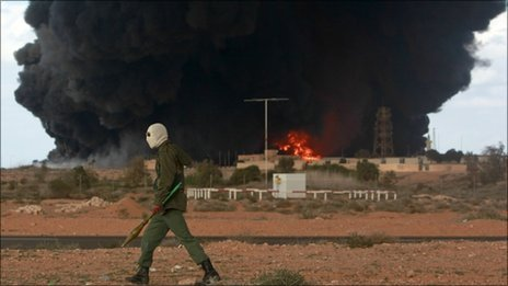 A rebel walking past a burning oil terminal