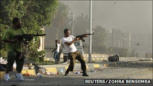 Libyan rebel fighters fire their weapons in Abu Salim district in Tripoli