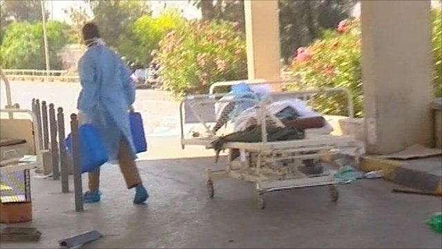 Hospital worker and body on a trolley
