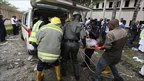 Emergency services personnel carry a victim into an ambulance