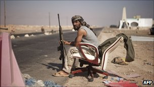 Rebel fighter sits at a checkpoint at the entrance of the oil port city of Ras Lanuf (27 August 2011)