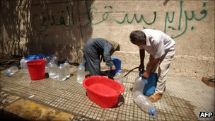 Men fill plastic jerry-cans with water from a public tap in Tripoli (27 August 2011)