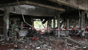 A soldier stands guard next to the damaged UN headquarters in Abuja (27 August 2011) 