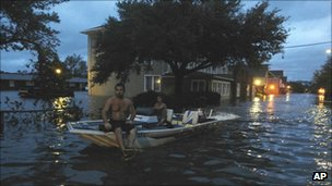 Two men use a boat to explore a street flooded by Hurricane Irene in Manteo, North Carolina on 27 August 2011