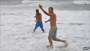 Two men enjoy the rough surf at the beach in Nags Head, North Carolina, on 27 August 2011