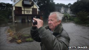 Tom Marshall takes a picture of his flooded home as he stands in floodwater in Kill Devil Hills, North Carolina