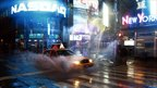 Taxi drives through flooded road in New York's Times Square.