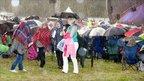 Concert-goers under umbrellas