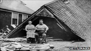 A couple sitting amongst the remains of their home at Highland Park, Rhode Island, USA, after a 100-mile-an-hour storm swept the Atlantic coast of North America in 1938