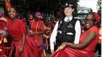 A police officer with revellers at the Notting Hill Carnival