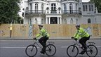 Two police officers cycle past a house with a wooden hoarding in front of it
