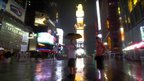People wait for a cab at Times Square in New York as rains fall before Hurricane Irene