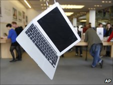 An Apple MacBook is seen on display as customers browse an Apple retail store in central London