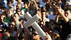 A man holds up a white cross during a protest against violence in Monterrey 28 August 2011.