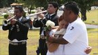 Mariachis play their instruments as people mourn during the funeral of a victim of an arson attack in Monterrey 28 August, 2011.