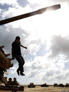 A rebel fighter jumps from a T-55 tank in Misrata on 29 August 2011