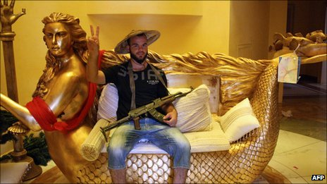 A Libyan rebel poses on a golden mermaid couch belonging to Aisha Gaddafi, daughter of Libya's leader Col Muammar Gaddafi, at her house in Tripoli on 26 August.