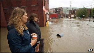 Two women overlook a flooded stretch of Burlington, Vermont