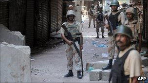 Pakistani paramilitary soldiers cordon off a street during house to house search operations against criminals in a troubled area of Karachi on August 28, 2011.