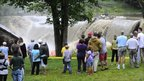 Residents in Windsor, Vermont, watch as water rushes over the Ascutney Mill Dam on Kennedy's Pond, on 28 August 2011