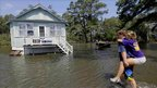 Residents of Stumpy Point, NC make their way into their flooded home on 28 August
