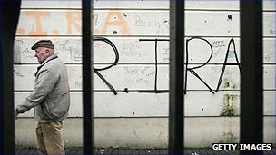 Man walking by IRA graffiti