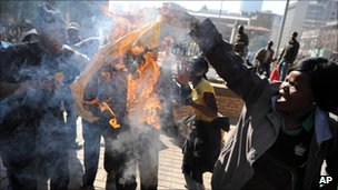 Malema supporters burn a party T-shirt with a portrait of South African President Jacob Zuma in downtown Johannesburg, 30 August 2011