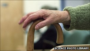 Old person's hand on walking stick