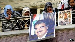 Lebanese women behind posters of former PM Rafik Hariri