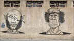 Graffiti depicting Muammar Gaddafi and his son Saif al-Islam (L) decorate a wall in Tripoli, Libya, 30 August 2011