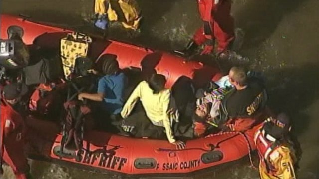 Families being taken to safety in inflatable boat, New Jersey