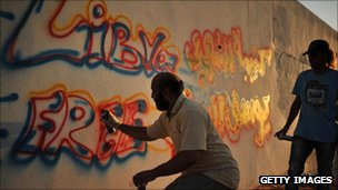 Libyans paint anti-Gaddafi grafitti in Tripoli