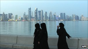 Qatari women in front of skyline of Doha