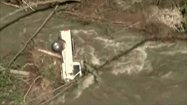 Truck on its side among debris in flooded river